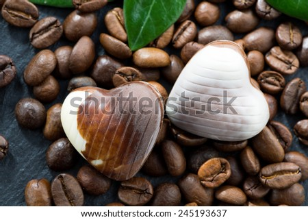 coffee beans and chocolate candies in a heart shape, close-up, horizontal - stock photo