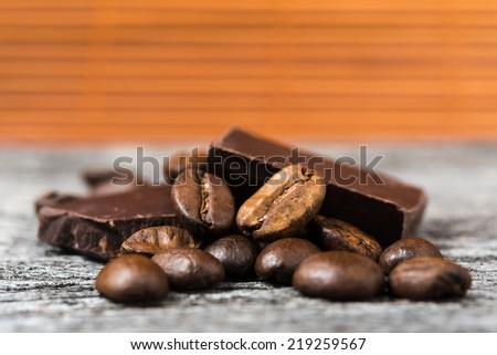 coffee beans and  chocolate on wooden background - stock photo