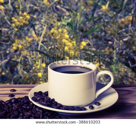 Coffee beans and coffee in white cup on wooden table opposite a defocused blossom background. Collage. Selective Focus. Toned. - stock photo