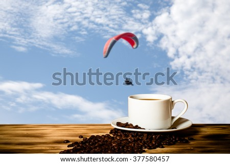 Coffee beans and coffee in white cup on wooden table opposite a defocused blue sky for background. Collage. Selective focus. - stock photo