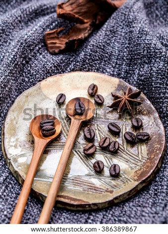 Coffee beans and star anise in ceramic plate with wooden spoons on dark fabric . - stock photo