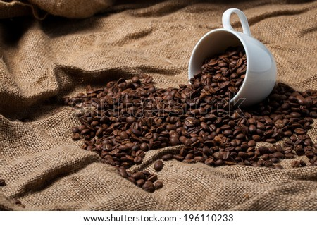 Coffee beans and white coffee cup on the burlap - stock photo