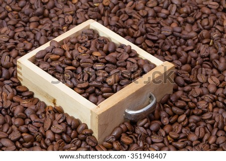 Coffee beans and wooden drawer on the table - stock photo
