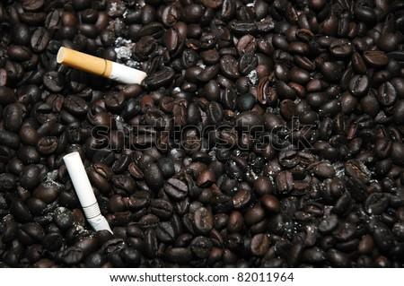 coffee beans as the ashtray to neutralize cigarette smoke - stock photo