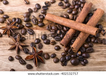 coffee beans, cinnamon and star anise on wood - stock photo