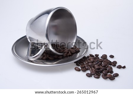 Coffee beans, cup and saucer - stock photo