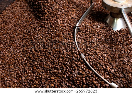 Coffee beans during the roasting process, screened and cooled inside the hopper after roasting, drum type roaster - stock photo