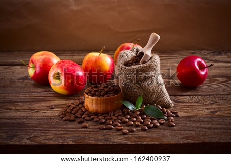 Coffee beans in a bag, scattered on a wooden table and a number of red apples. Free space for your text - stock photo