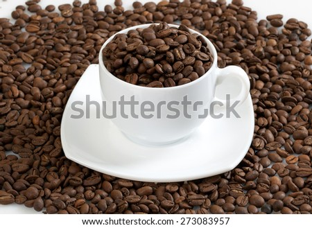 Coffee beans in a cup on the table and on a white background. - stock photo