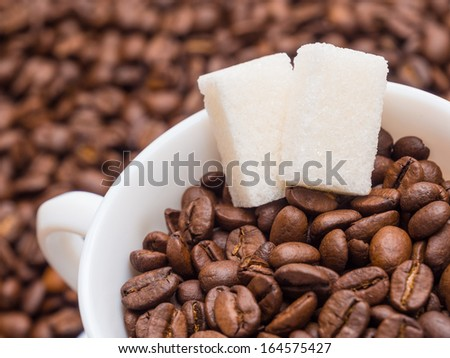 Coffee beans in a cup with pieces of sugar - stock photo