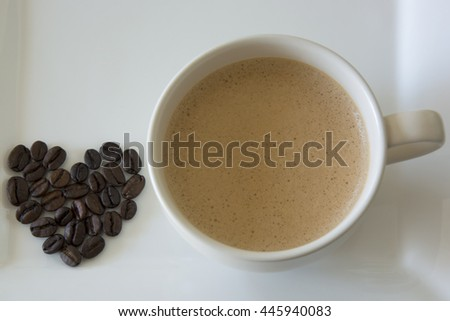 Coffee beans in a heart shape besides a cup of coffee - stock photo