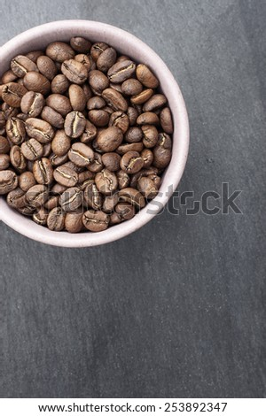 Coffee Beans in a Pink Cup on a Slate Background. With Copy Space. - stock photo