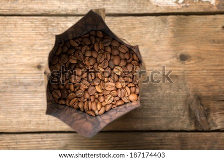 Coffee beans in aluminum foil bag package on wooden surface - stock photo
