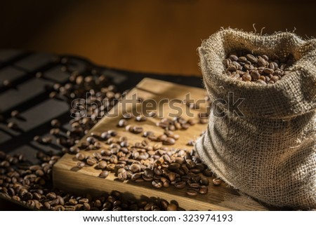 coffee beans in bag on wood - stock photo