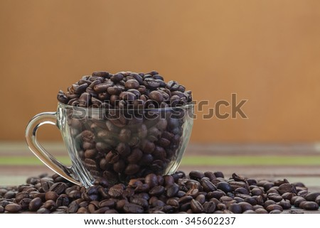 Coffee beans in clear coffee cup on grunge brown background - stock photo