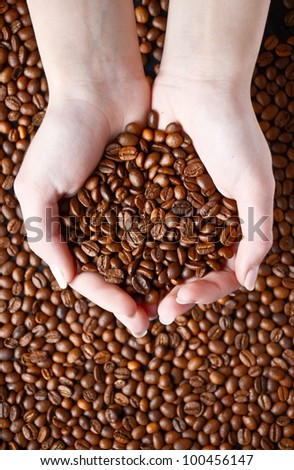 Coffee beans in hand - stock photo