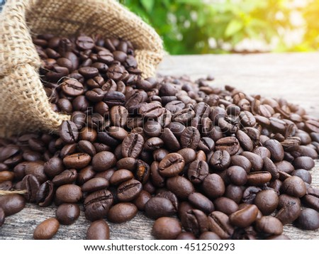 Coffee Beans in Sack Bag on Wood Background - stock photo