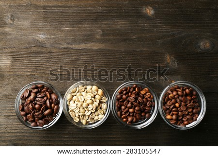 Coffee beans in saucers on wooden background - stock photo
