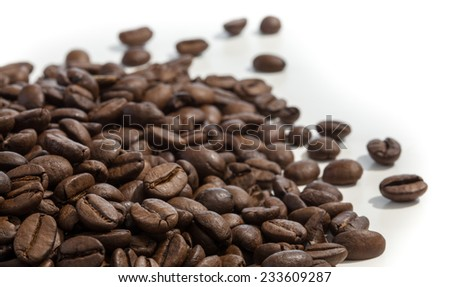coffee beans lying on a white table with shallow depth of field - stock photo