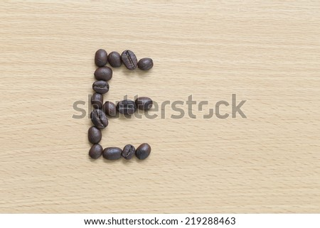 Coffee beans of alphabet placed on the wood background. - stock photo