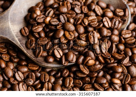 Coffee beans on a wooden spoon - stock photo