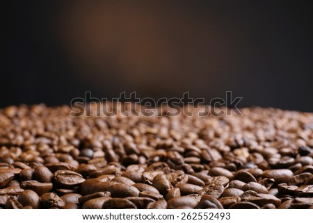 Coffee beans on brown background - stock photo