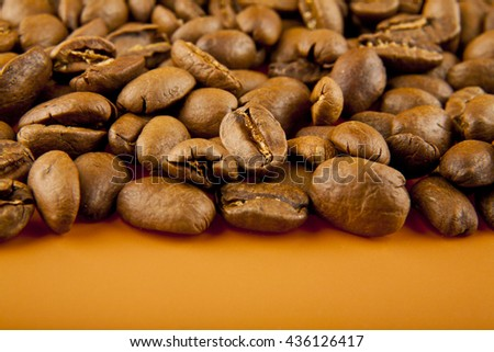 coffee beans on brown background closeup - stock photo