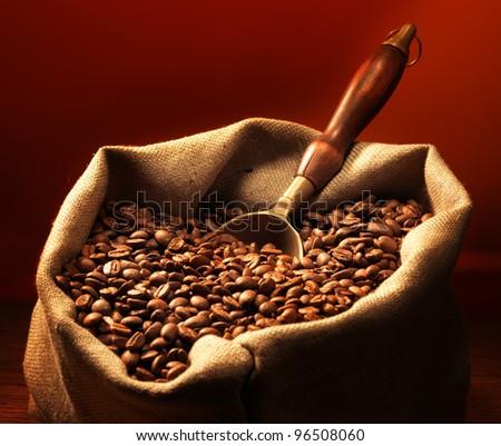 Coffee beans on burlap sack with metal scoop - stock photo