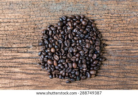 Coffee beans on old wood table - stock photo