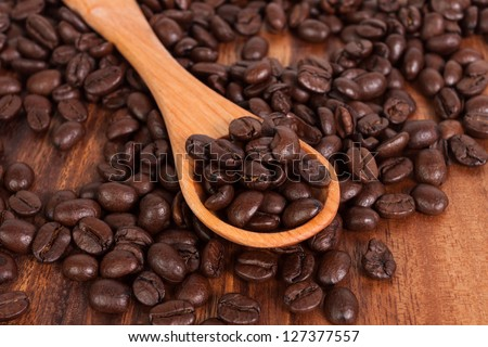 Coffee beans on wood spoon, isolated on wooden board - stock photo