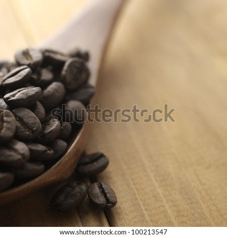 coffee beans on wooden spoon - stock photo