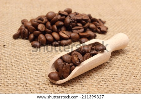 Coffee beans on wooden spoon and heap of coffee in background, coffee grains. Background texture of old jute  - stock photo