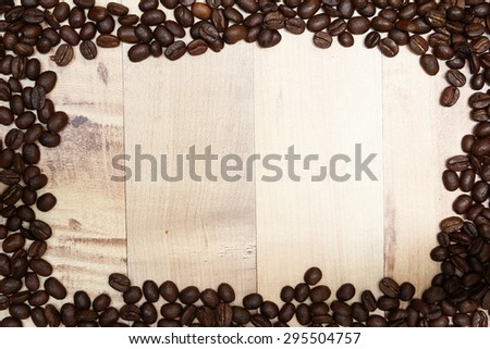 Coffee beans on wooden surface - stock photo