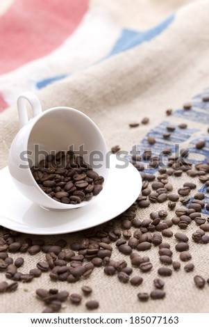 Coffee beans scattered across a table surrounding a cup and saucer. - stock photo