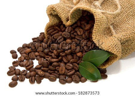 Coffee beans spilled out of the jute bag with green leaves on white background - stock photo