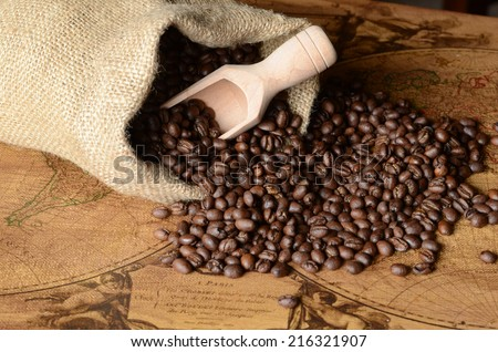 Coffee beans spilling from a burlap bag and a scoop on a textured map surface - stock photo