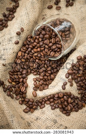 Coffee beans spilling from glass cup - stock photo