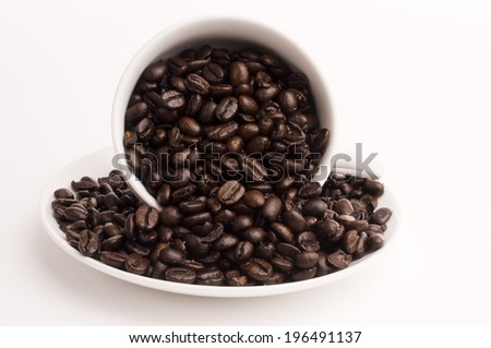 Coffee beans spilling from inside a white cup onto a saucer. - stock photo