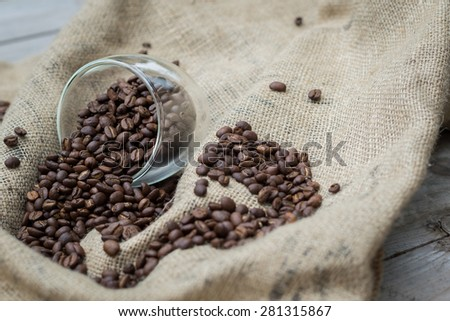 Coffee beans spilling out of glass - stock photo