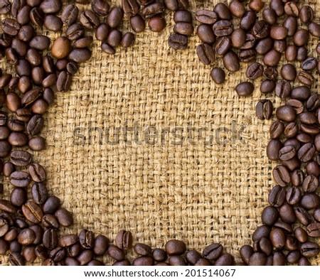 Coffee beans surrounding on burlap sack - stock photo