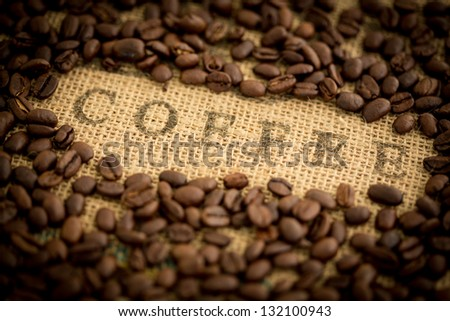 Coffee beans surrounding the word coffee stamped on burlap sack - stock photo