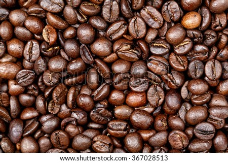 Coffee beans texture background. Closeup of fresh roasted bag of dark roast coffee beans pattern, useful for text copy space, element detail or advertisement background. - stock photo