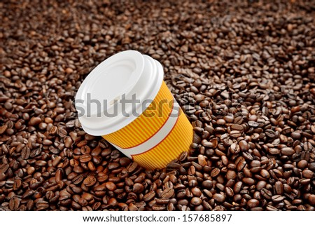 Coffee beans with a disposable cup - stock photo