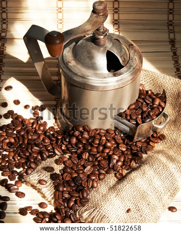 Coffee beans with an old coffee grinder - stock photo