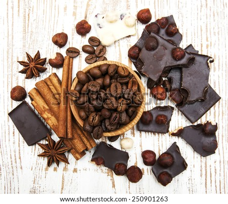 Coffee beans with cinnamon sticks,  chocolate and nuts - stock photo