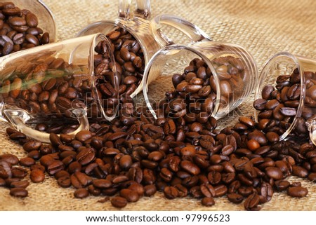 coffee beans with  coffee cups on the table - stock photo