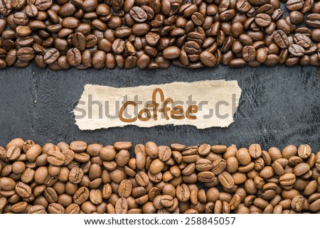 Coffee beans with Coffee label on black wooden background. - stock photo
