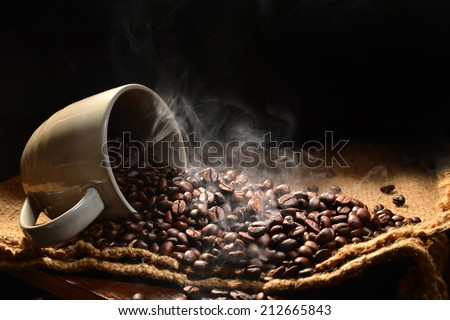 Coffee beans with smoke in coffee cup - stock photo