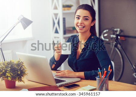 Coffee break. Attractive young woman holding coffee cup and smiling while sitting at her working place in office  - stock photo
