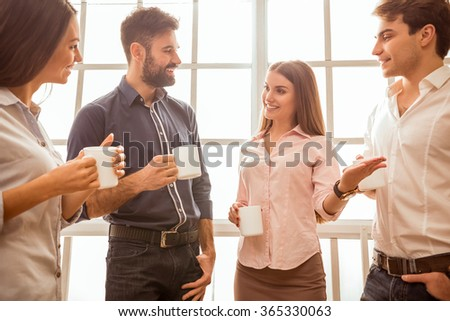 Coffee break chat. Group of attractive business people, standing next to each other, holding a cups, smiling standing at the window - stock photo